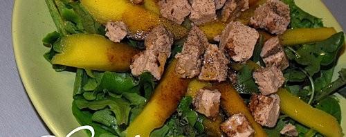 une assiette avec salade de mache, mangue tranchée et foie gras
