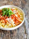 une assiette de macaronis sauce tomate, roquette et lardons