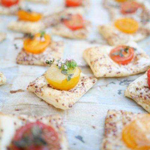 un plateau de petits feuilettés à la moutarde à l'ancienne et aux tomates cerises à servir à l'apéro