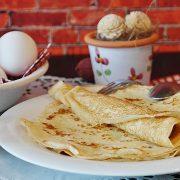 des crêpes posées dans une assiette, avec des oeufs en fond et de la farine : tout pour faire les crepes