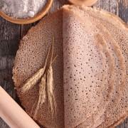 des galettes au sarrazin posées sur un plan de travail à côté d'un rouleau à patisserie et de farine