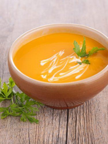 Un bol de soupe de potiron avec un trait de crème fraiche et des herbes aromatiques