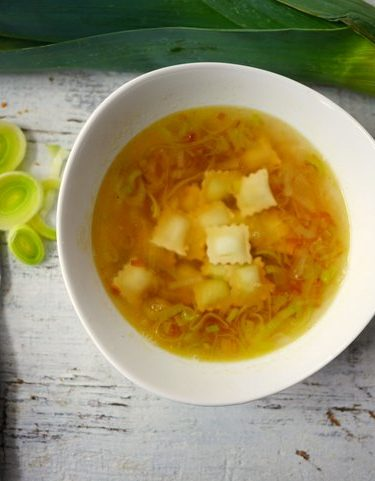 Un bol de soupe de ravioles aux poireaux, posé sur une table blanche, avec es morceaux de poireaux émincés posés sur la table à côté d'un couteau de cuisine