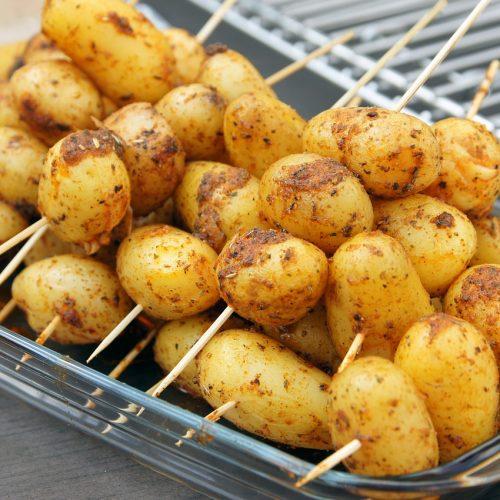 des pommes de terre piquées sur des batonnets en bois pour le barbecue