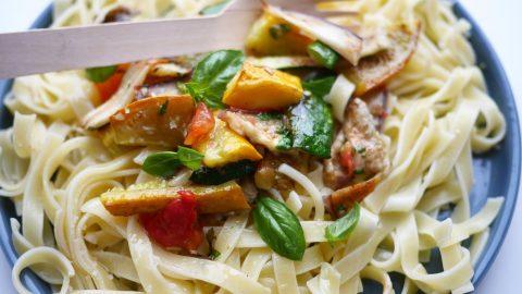une assiette de pâtes aux légumes d'été grillés et au basilic