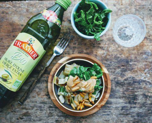 Une bouteille d'huile d'olive bio posée à côté d'un bol de bletttes sautées au tahiné