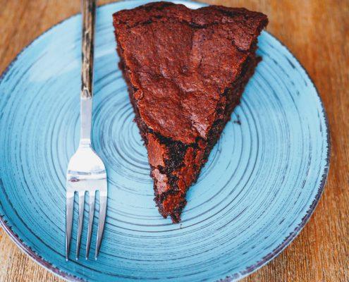 une part de gâteau au chocolat noir posée dans une assiette