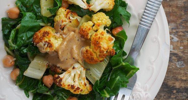 une assiette contenant des verts de blettes sautés à l'huile, servies avec du chou fleur rôti au four, des pois chiches et du houmous