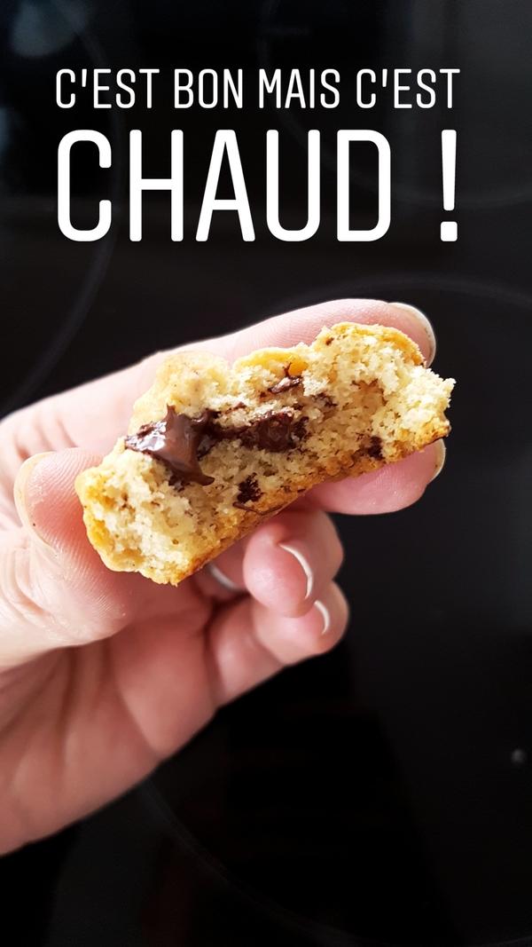 un cookies tout juste sorti du four, croqué à pleine dent où l'on voit le chocolat dégouliner