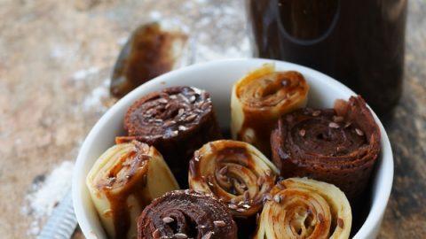 des crêpes à la vanilles et des crêpes au chocolat coupées en rouleaux, déposées dans un bol blanc et nappées de confiture de potiron