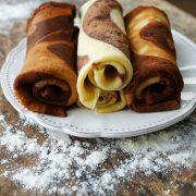une assiette blanche posée sur un plan de travail fariné, contenant 3 crêpes tourbillon vanille et chocolat