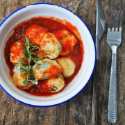 une assiette posée sur un plan de travail avec des couverts, contenant des boulettes de ricotta aux blettes, servies dans une sauce tomates au citron et au romarin