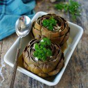 un plat à four avec deux gros artichauts verts farcis de légumes
