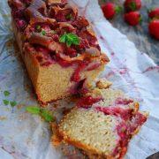 Un cake aux fraises tranché, parsemé de feuilles de menthe