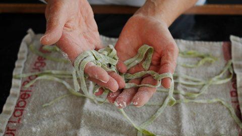 des mains en train de tenir des pâtes fraiches fait maison aux épinards