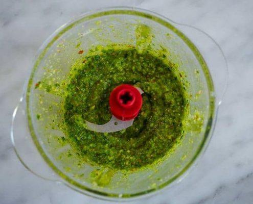 Un bol de mixer contenant du pesto vert d'ai des ours