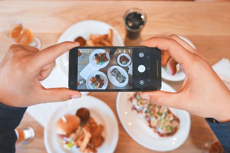 Un smartphone en train de photographier une scène culinaire