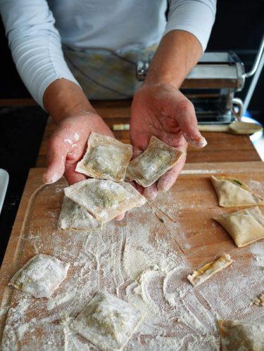 Des mains tenant des raviolis fait maison au dessus d'un plan de travail fariné
