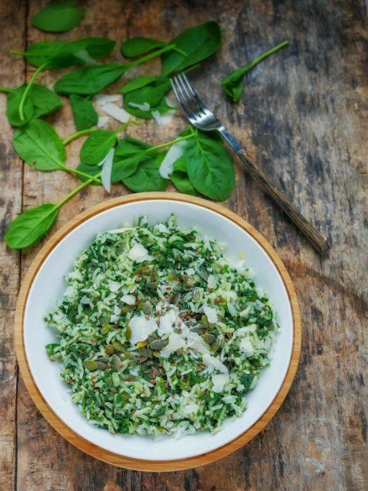 Une assiette de risotto d'épinards avec du parmesan et des graines de courges et de lin