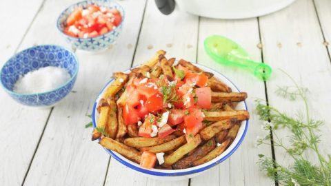 une assiette de frites maison avec des dès de tomate, de la féta et de la coriandre
