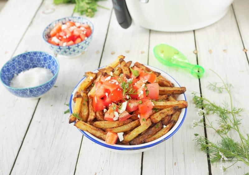 une asseiette de frites maison avec des dès de tomate, de la féta et de la coriandre