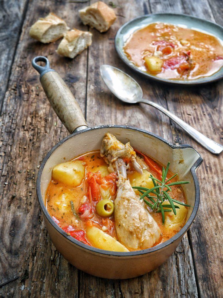 Une casserole en fonte avec un ragout de pommes de terre tomates olives et poulet