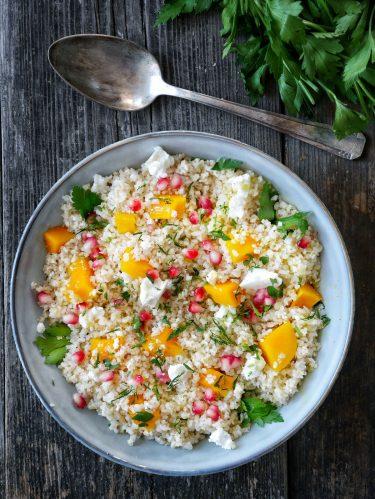 Un plat de salade de boulgour, dés de ptoimarron, feta et grenade