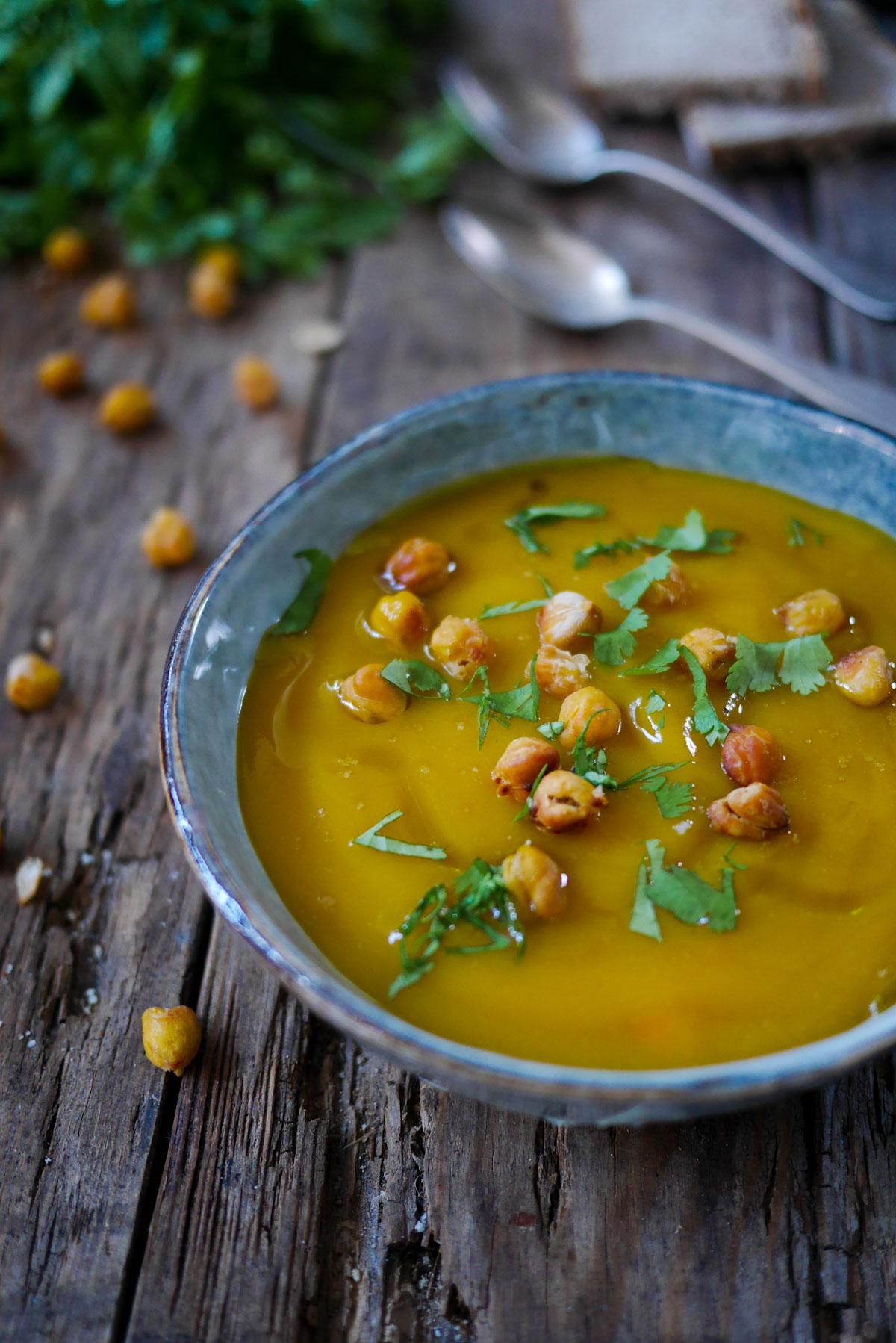 Un bol de soupe de carottes houmous et pois chiches grillés